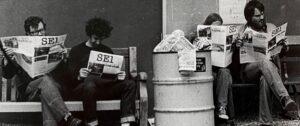 Four people reading SE1 newspaper next to bin of other papers.